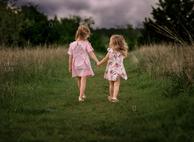 Two little girls walking hand in hand in a field