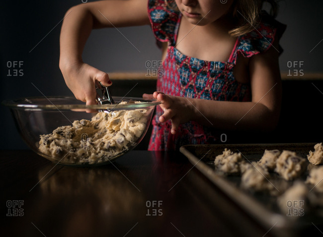 Little girl scooping chocolate chip cookie dough onto a pan