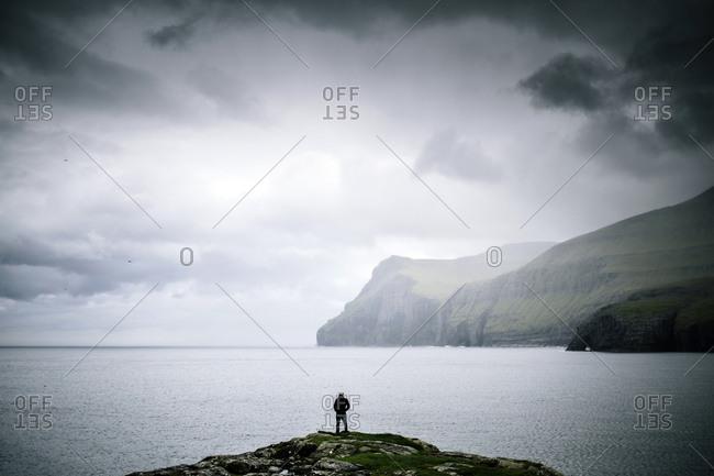Faroe Islands - July 29, 2014. A person is enjoying the horizon in the Faroe Islands.