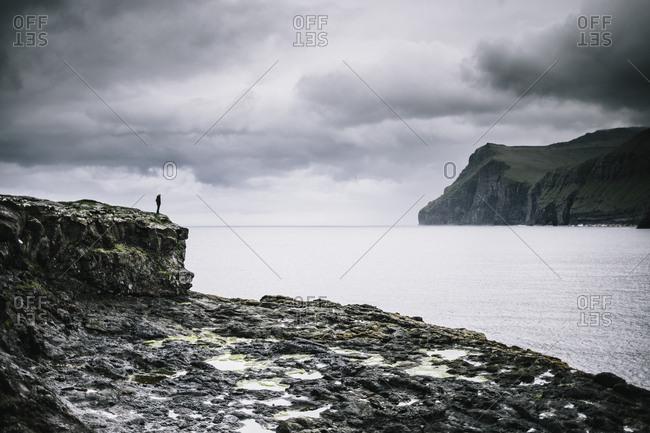 Faroe Islands - July 29, 2014. A person is enjoying the beautiful landscape in the Faroe Islands.
