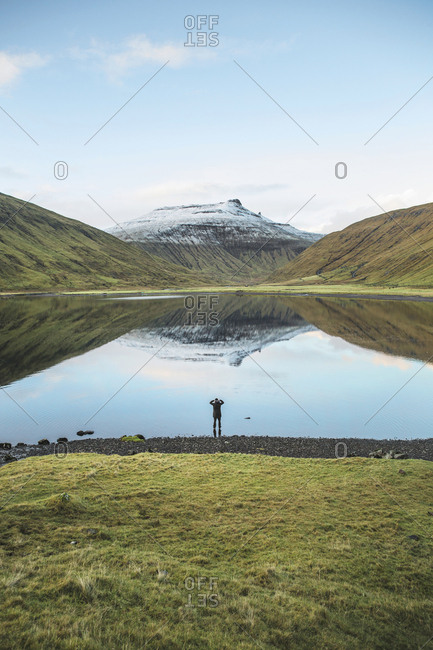 Faroe Islands - November 19, 2015. A person is enjoying the view of the mountains and lake in the Faroe Islands.