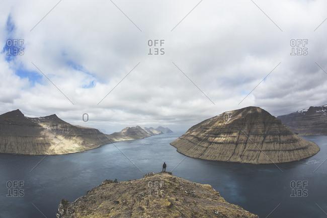 Mykines, Faroe Islands - May 12, 2016. A person is watching the beautiful landscape. Mykines is one of the 18 main islands of the Faroe Archipelago.