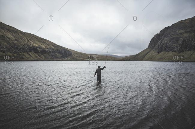 Mykines, Faroe Islands - May 10, 2016. A person is fishing in a lake at the Faroe Islands.