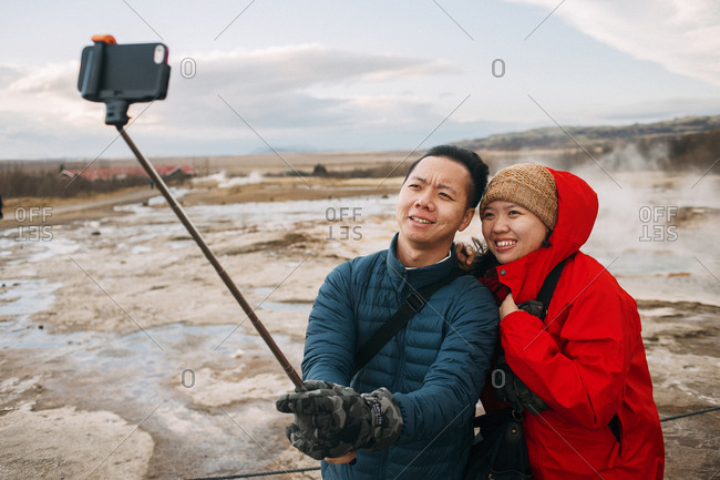 Iceland - November 13, 2014. A smiling Asian couple is taking a selfie with a Selfie stick at the Strokkur geyser in Iceland