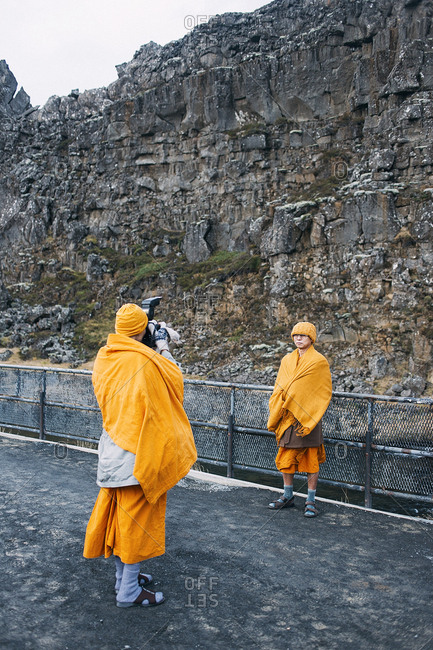 Iceland - November 13, 2014. A Buddhist monk is photographing another monk in Thingvellir, Iceland.