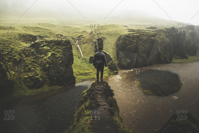 Iceland - September 26, 2015. A person is standing on the mountain peak and enjoying the beautiful view of Fjadrargljufur, which is a canyon in south east Iceland.