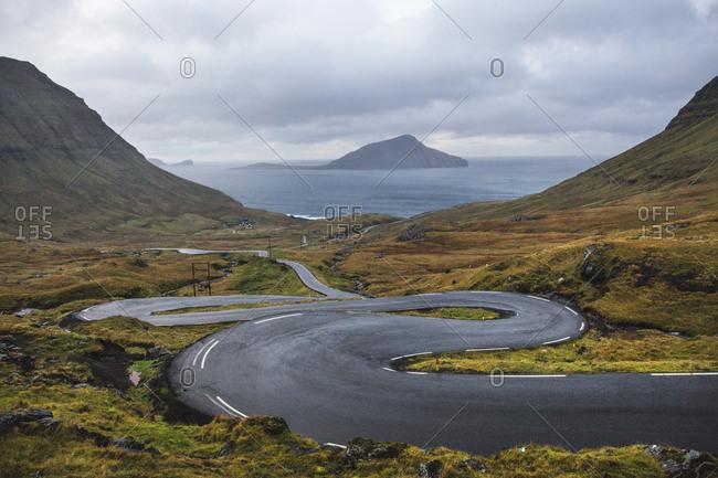 Faroe Islands - November 17, 2015. An empty road in the beautiful mountainous landscape of the Faroe Islands.
