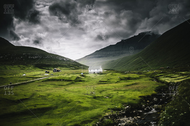 Faroe Islands - July 24, 2014. A village of a few houses is surrounded by beautiful green mountains in the Faroe Islands.