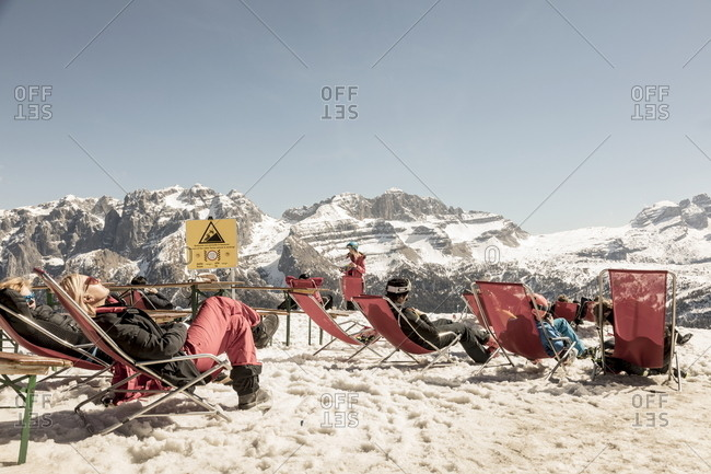 Trentino, Italy - March 25, 2017: Skiers lounging in chairs  in Alps