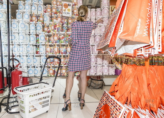 Milan, Italy - April 13, 2017: Woman picking out canister of candy