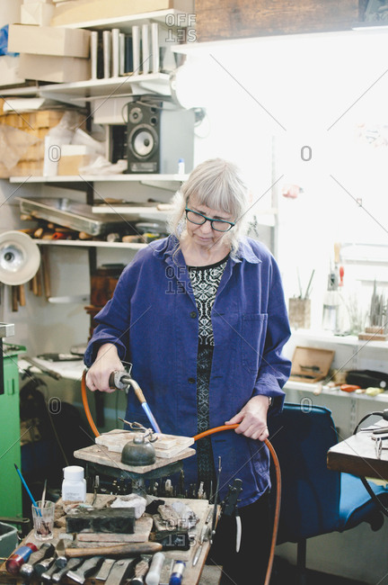 Senior female craftsperson using blowtorch for metalworking in jewelry workshop