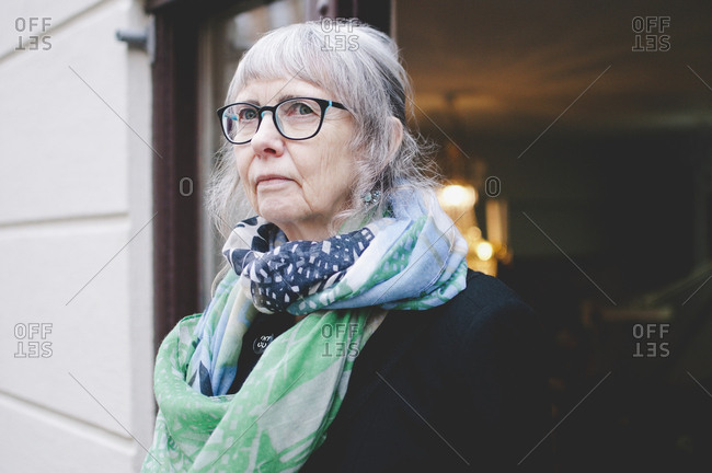 Thoughtful female craftsperson wearing scarf while standing outside jewelry shop