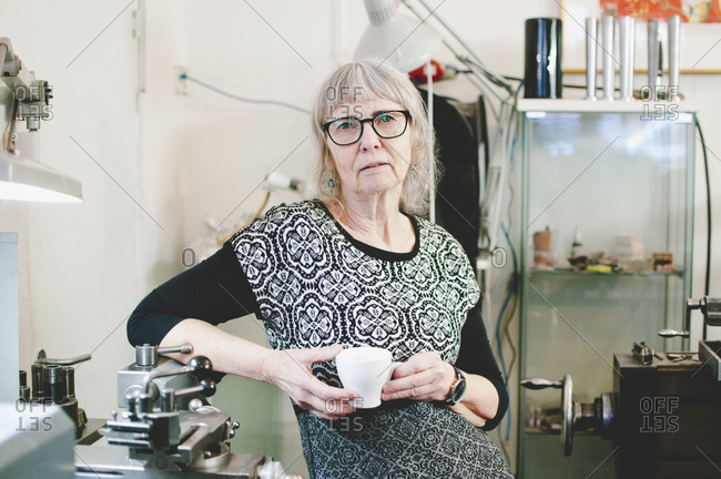 Portrait of confident senior woman holding coffee cup in jewelry shop