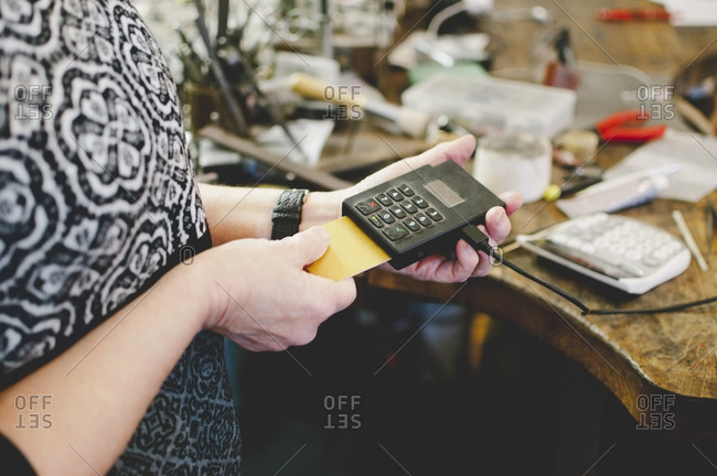 Midsection of senior woman using credit card reader in jewelry workshop