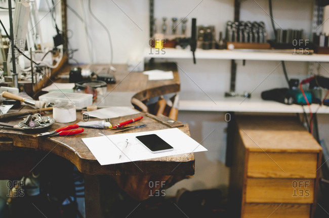 Mobile phone and document on workbench in jewelry workshop