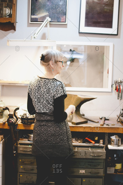 Rear view of female craftsperson standing at workbench in jewelry workshop