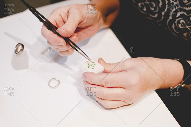 Cropped image of senior female craftsperson assembling jewelry in workshop