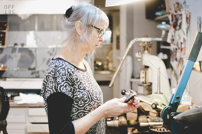 Side view of senior woman using caliper in jewelry workshop