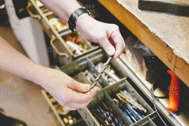 Cropped image of senior craftsperson holding drill bit in jewelry workshop