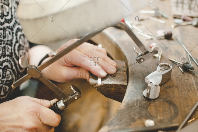 Cropped image of senior woman cutting metal with hand saw in jewelry workshop