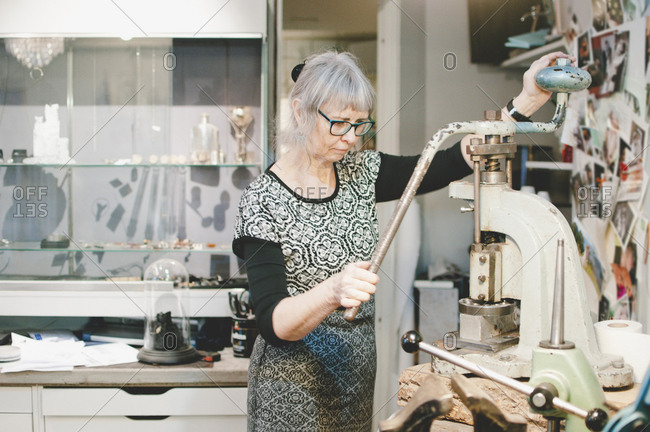 Senior woman working on vise grip in workshop