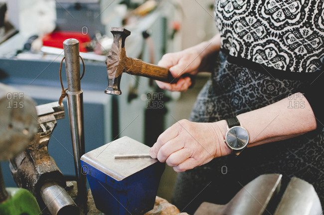 Midsection of senior woman hammering on metal to make jewelry in workshop