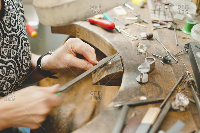 Cropped image of senior craftsperson making jewelry in workshop