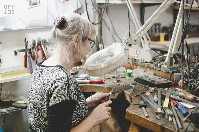 Side view of senior woman making jewelry at workbench in workshop