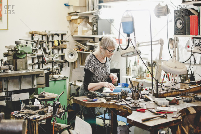 Senior female craftsperson working at workbench in jewelry workshop