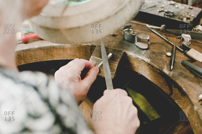 High angle view of senior female jeweler working at workbench in workshop