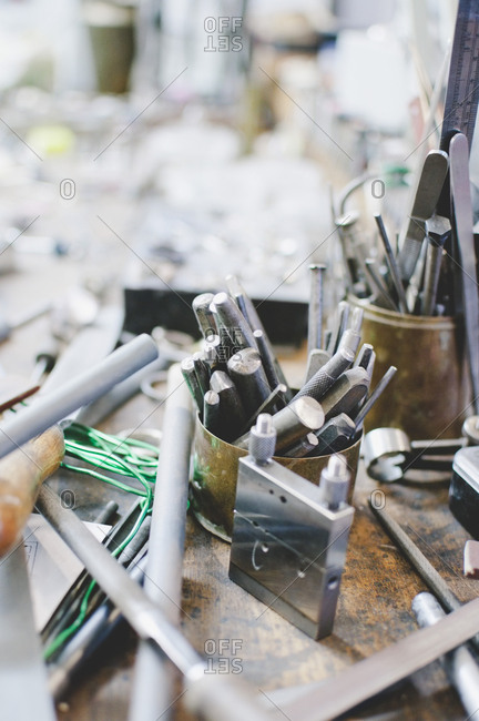High angle view of various tools in container on workbench at jewelry workshop