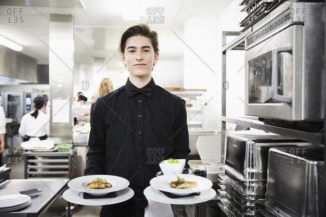 Portrait of confident waiter holding dishes in commercial kitchen