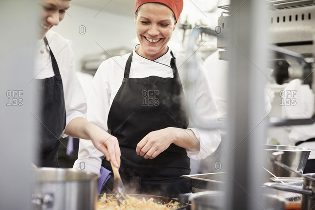 Teacher watching female chef student cooking food in kitchen at restaurant
