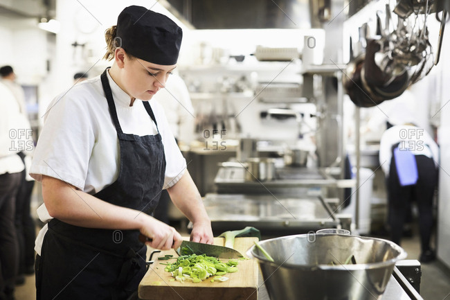 Young female chef chopping vegetables on cutting board in cooking school