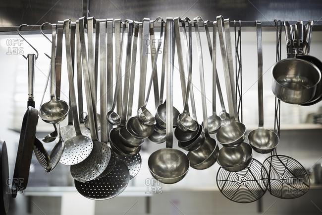 Utensils on metal rack in commercial kitchen