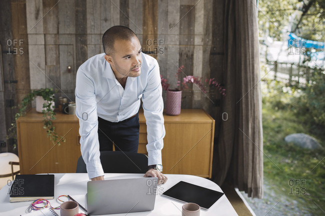 Businessman looking away while using laptop at desk in portable office truck