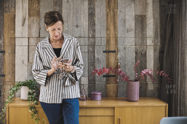 Businesswoman using smart phone against wood paneling in portable office truck