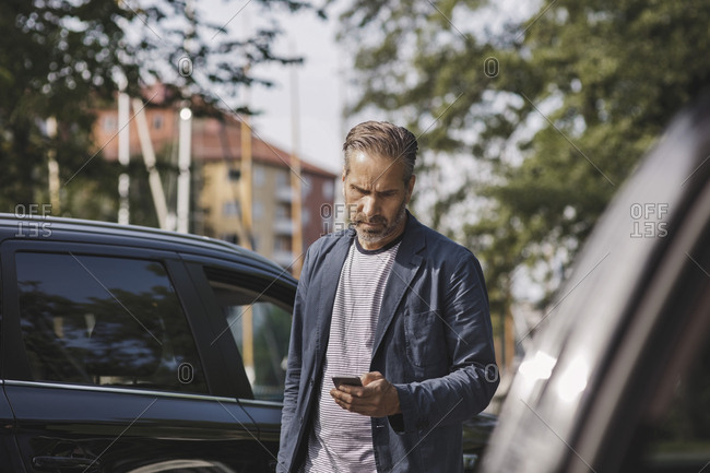 Businessman using smart phone while standing by cars at park