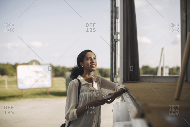 Young businesswoman holding mobile phone while standing by portable office truck
