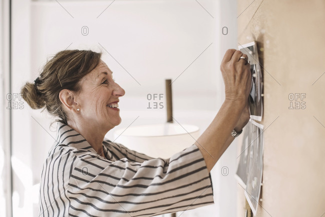 Smiling senior businesswoman pinning photograph on bulletin board in portable office truck