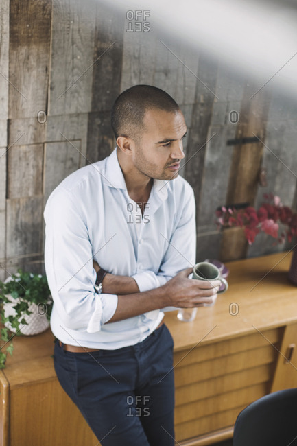 High angle view of businessman holding coffee cup while standing in portable office truck