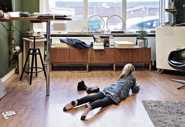 Rear view of girl lying on hardwood floor at eyeglasses workshop