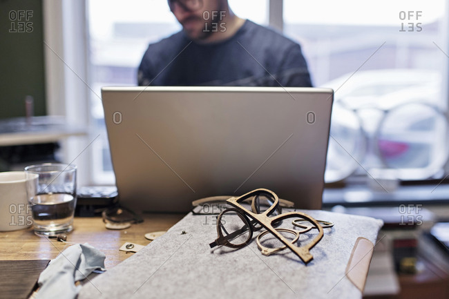Midsection of male owner using laptop at desk in eyeglasses workshop
