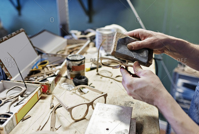 Cropped image of male owner rubbing eyeglasses with work tool at workshop