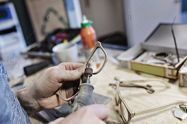 Cropped image of owner making eyeglasses with work tool at workshop