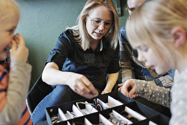 Family arranging eyeglasses in box at workshop