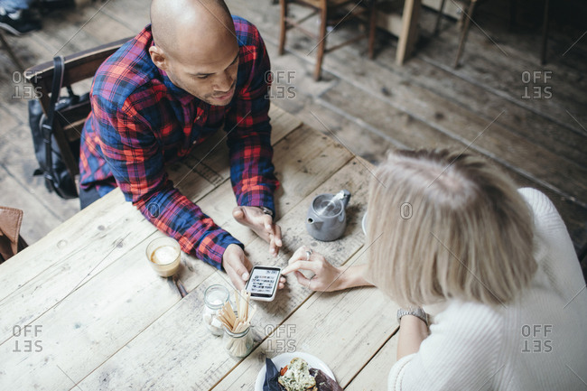 High angle view of multi-ethnic couple using mobile phone in coffee shop