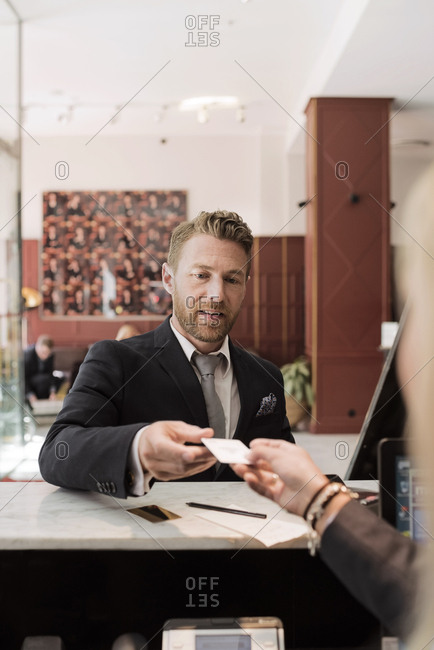Businessman giving credit card to receptionist at hotel reception