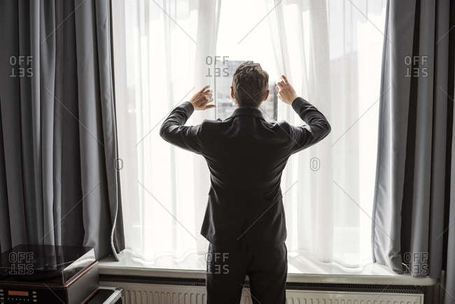 Rear view of businessman opening white curtain on window in hotel room