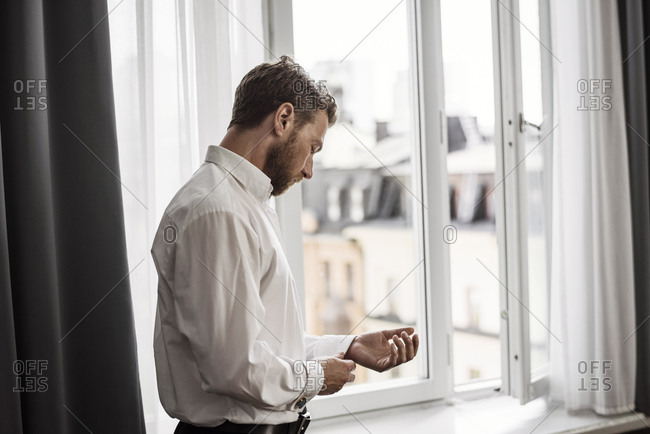 Side view of businessman getting dressed against window at hotel room